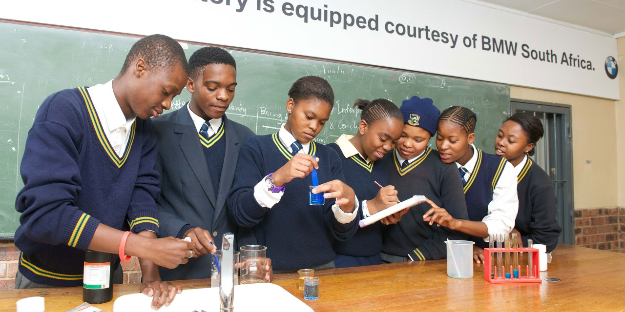 The picture shows a group of students doing a science experiment in a classroom at school.